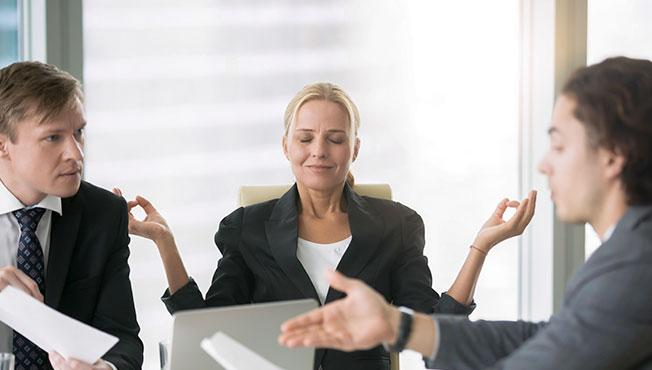 Business negotiation with men arguing and woman meditating.