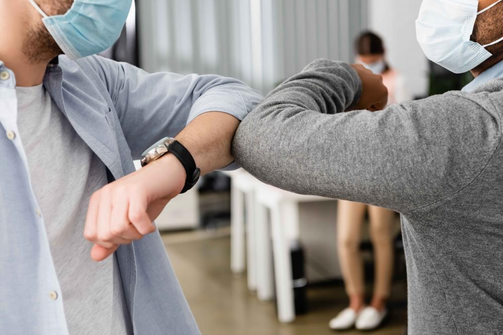 employees elbow touching due to covid