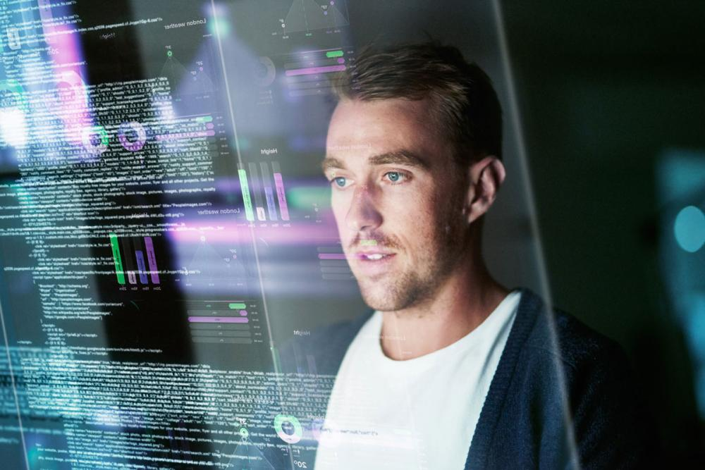 Man looking at coding on a screen