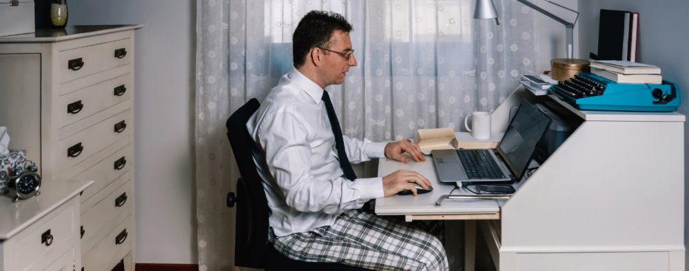 Man on a video call in his bedroom wearing a smart shirt and pajama pant bottoms