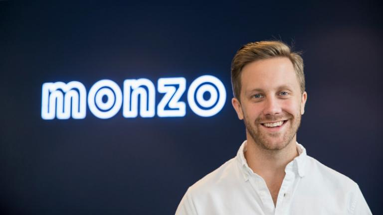 Photo of Monzo CEO Tom Blomfield next to company sign.