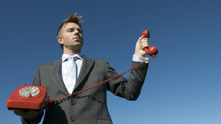 Businessman holding red phone