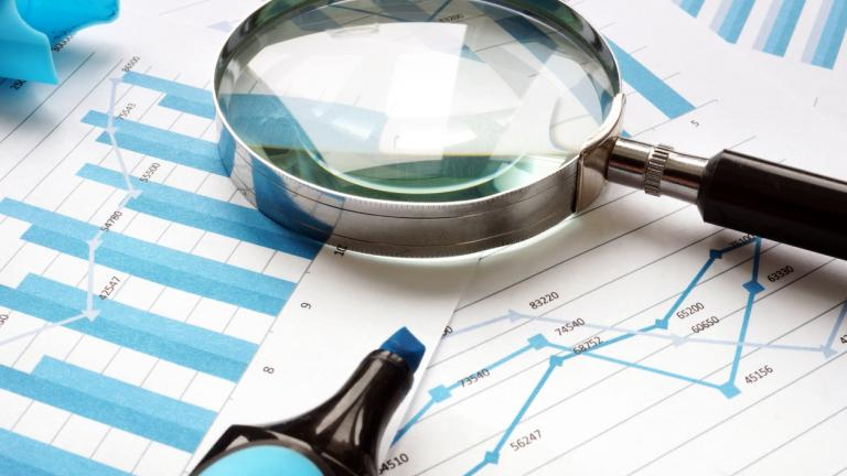 Magnifying glass and financial documents. Audit and accounting.