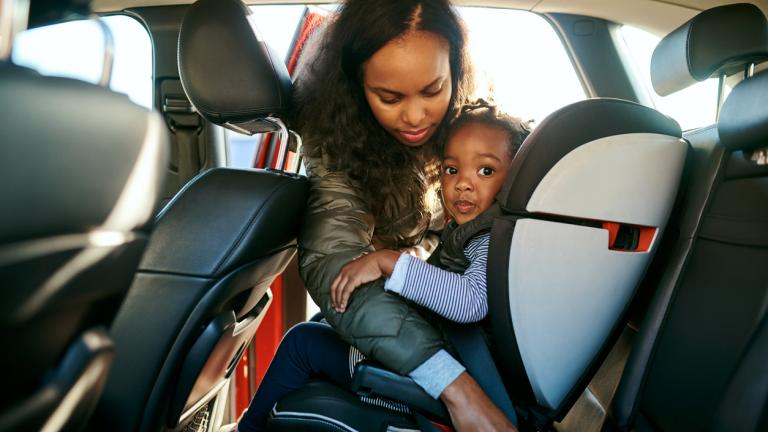 Shot of an adorable little girl being secured in her car seat by her mother