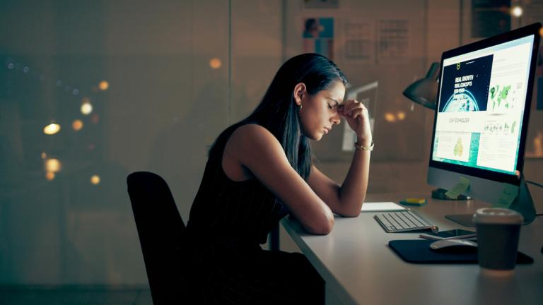 Shot of a young businesswoman looking stressed while using a computer at night in a modern office.