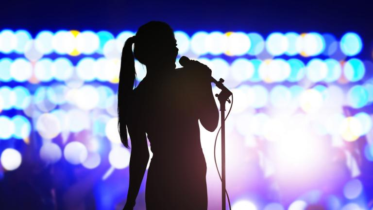 Woman with microphone singing on concert stage
