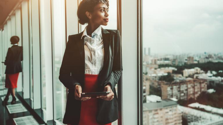 A black female entrepreneur holding a digital tablet is leaning against a panoramic window of an office business skyscraper and looking into the distance