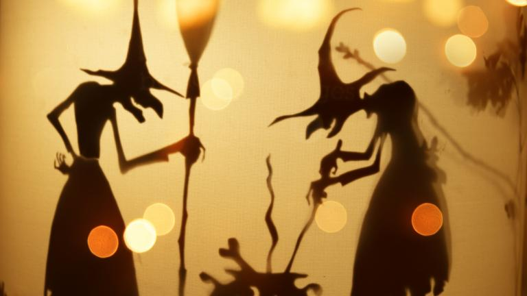 Silhouette of witches standing over cauldron