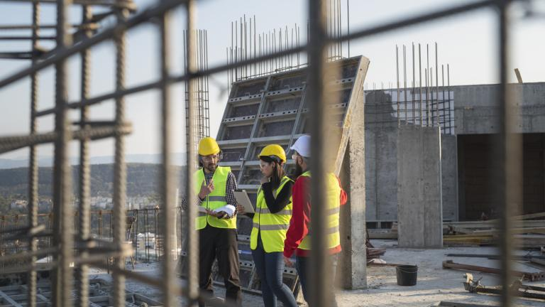 Domestic reverse charge: Construction workers standing on outdoor construction site and discuss the building plans.