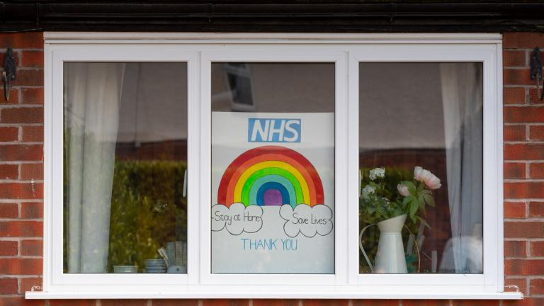 Rainbow drawings in window of house during Covid19