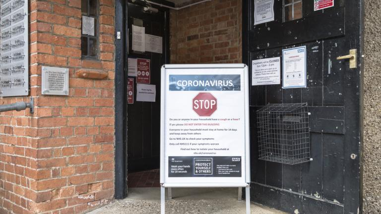 Coronavirus COVID-19 warning sign with prevention information outside a GP doctor surgery