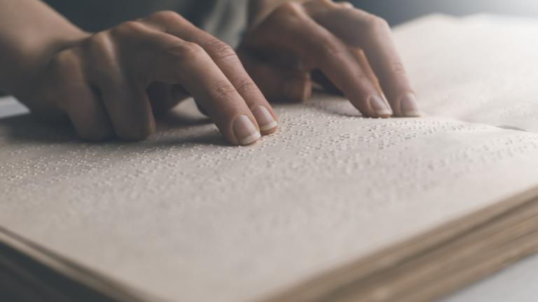 The hand of a blind man reads the text of a braille book.