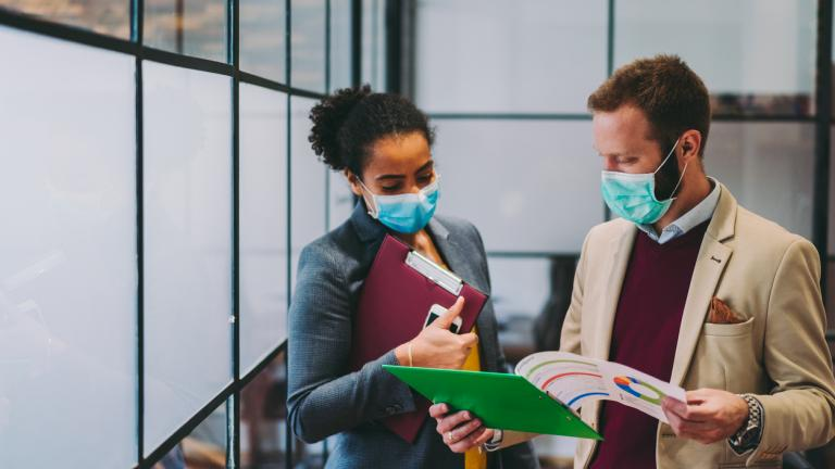Businesspeople wearing masks in the office for illness prevention during COVID-19 pandemic.
