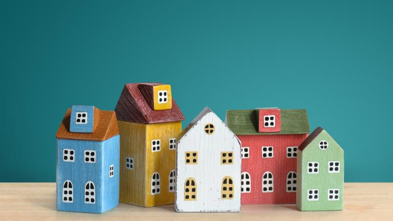 Wood miniature colorful houses on wooden table and green background. Mortgage, real estate, insurance concept.