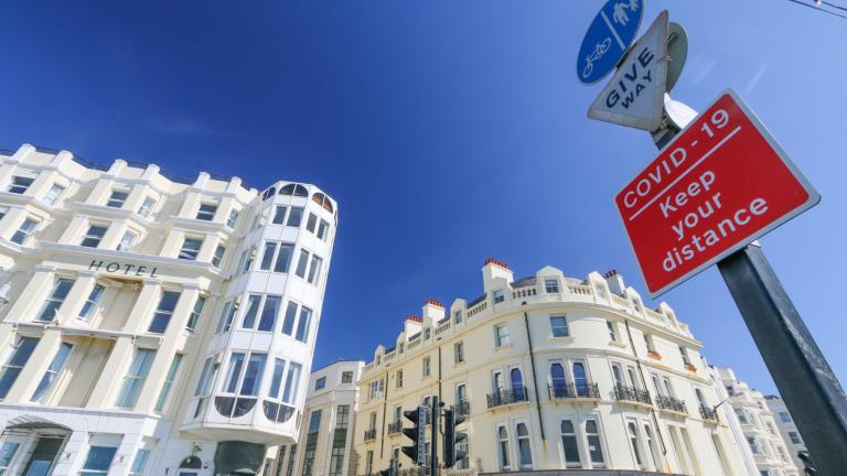 a Brighton hotel next to a coronavirus sign
