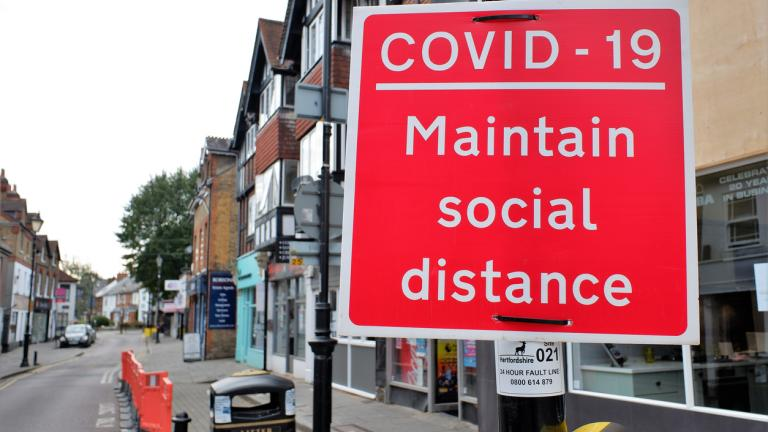 Covid-19 maintain social distance sign on UK shopping street