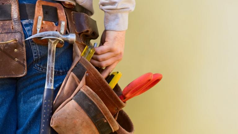 Construction Worker Reaches Into His Tool Belt