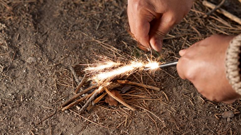Man starting fire using twigs survival
