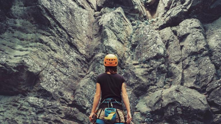 Risk calculating activities: Young woman wearing in climbing equipment standing in front of a stone rock outdoor and preparing to climb, rear view.