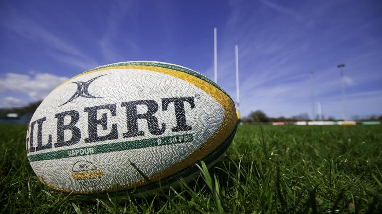 A rugby ball manufactured by Gilbert rugby, laying on a rugby pitch