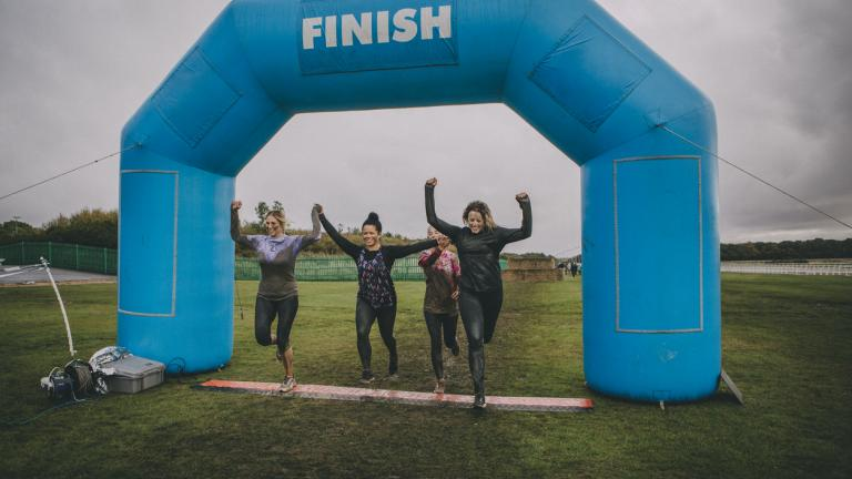 Group of friends are running over the finish line at a charity obstacle course.