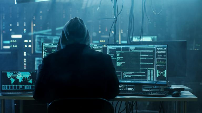 Dangerous Hooded Hacker Breaks into Government Data Servers and Infects Their System with a Virus. His Hideout Place has a Dark Atmosphere, Multiple Displays, Cables Everywhere.