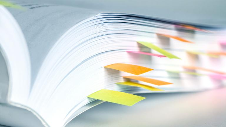 A white book marked by sticky notes
