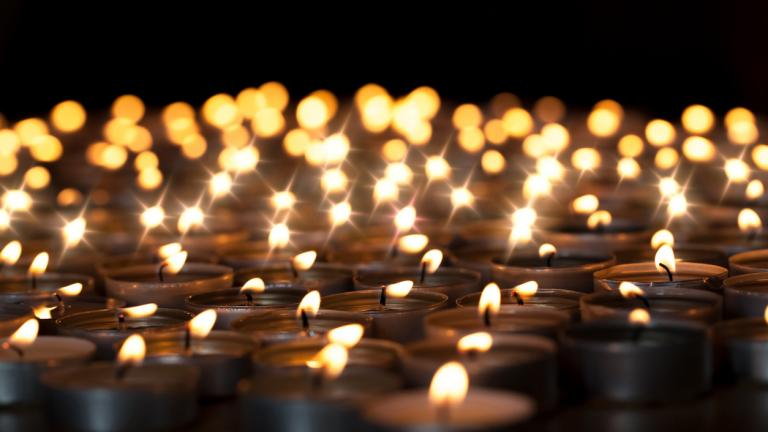 World religion day: Tealight candles. Beautiful Christmas celebration, religious, or remembrance candlelight image. Romantic candlelit vigil. Selective focus against black background.