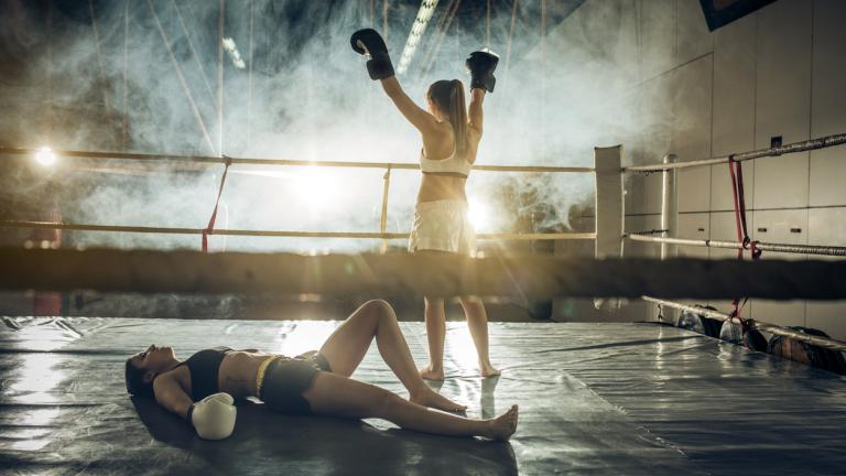 Back view of a female boxer celebrating victory after knocking out her opponent in a ring.