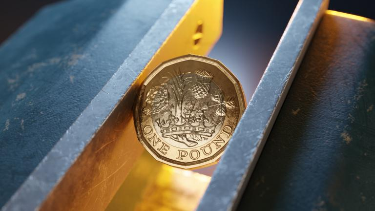 British pound coin held by a vice