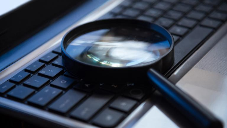 Selective focus on keyboard with magnifier searching concept in dark low key night tone. Searching, investigate concept