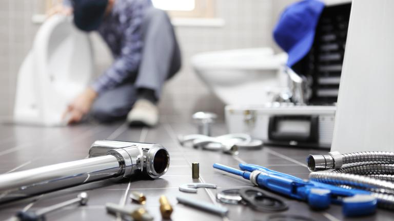 Plumber at work in a bathroom, plumbing repair service