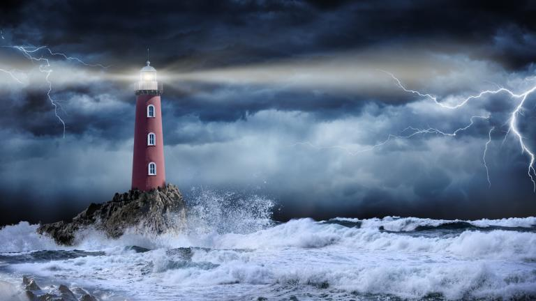 Lighthouse on a rock by the sea during a storm.