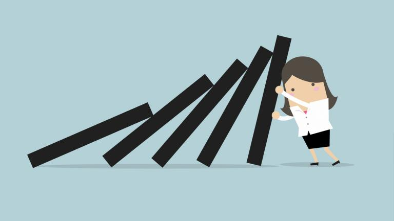 usinesswoman pushing hard against falling deck of domino tiles