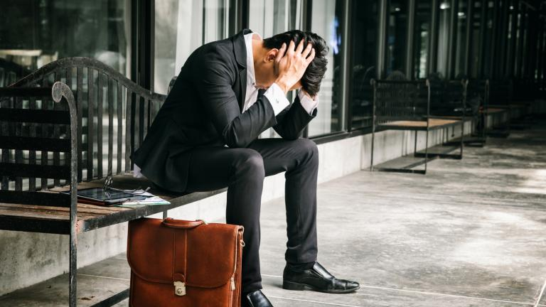 unemployed businessman sits alone in the corridor of an office
