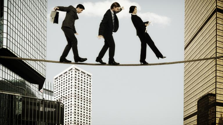 three business leaders on a tightrope