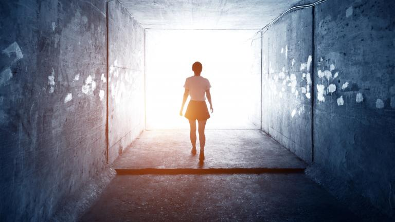 Woman walking through a dark tunnel