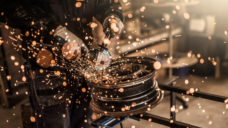 Mechanic grinding a damaged steel wheel close up