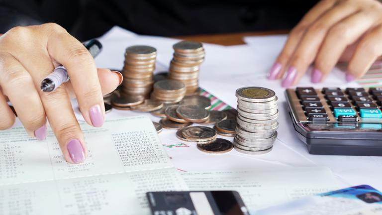 Businesswoman hand counting on saving account with stack of coins