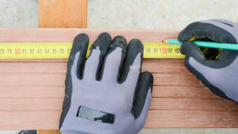 worker hands working with a measuring tape and pencil in wood