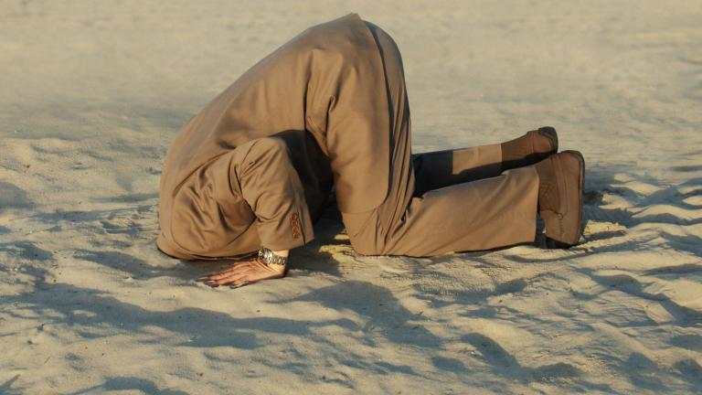 Businessman with head stuck in sand