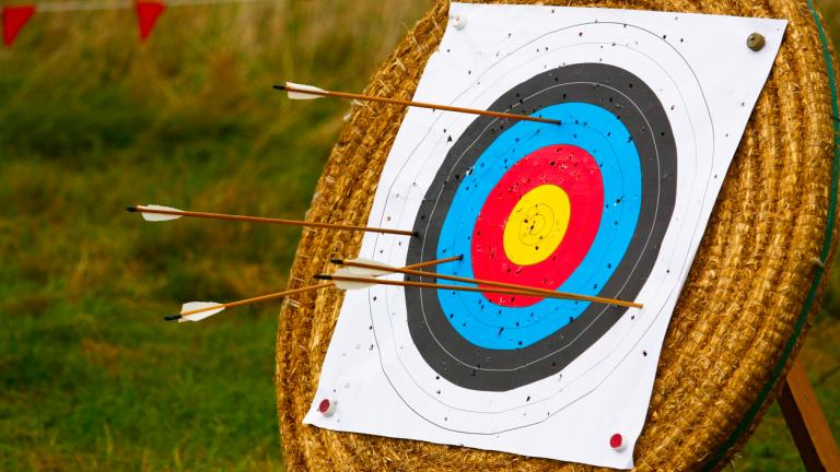 Target stand for archery with arrows in it and holes