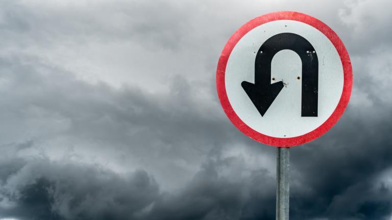 U turn sign on white dark cloud background