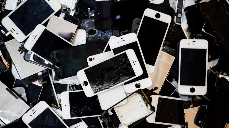 Stack of smart phones with cracked and damaged LCD screens