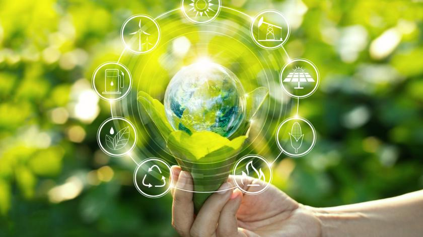Hand holding light bulb against nature on green leaf with icons energy sources for renewable, sustainable development.