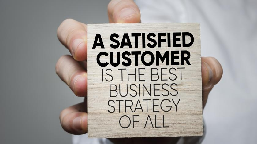 Using customer experience to drive growth - image of person holding a block with message -  a satisfied customer is the best business strategy of all