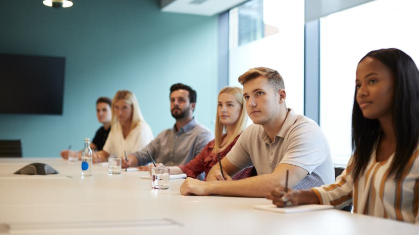 Group of young trainees sitting at boardroom
