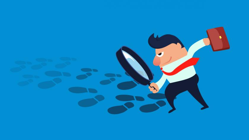 Businessman exploring the footprint with a magnifying glass