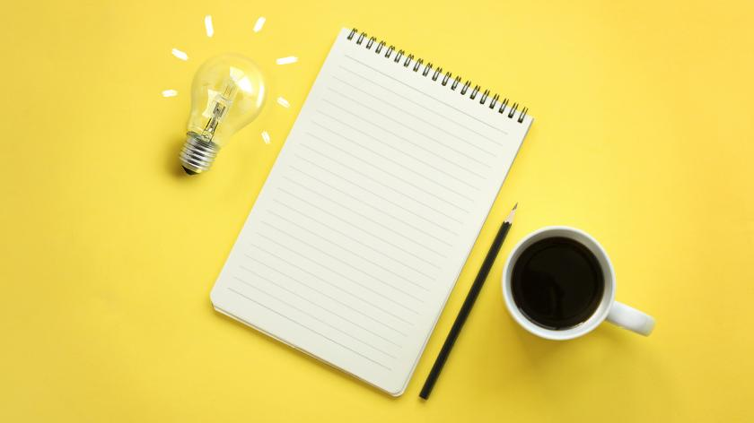 Flat lay of light bulb and empty memo pad and pencil on yellow background