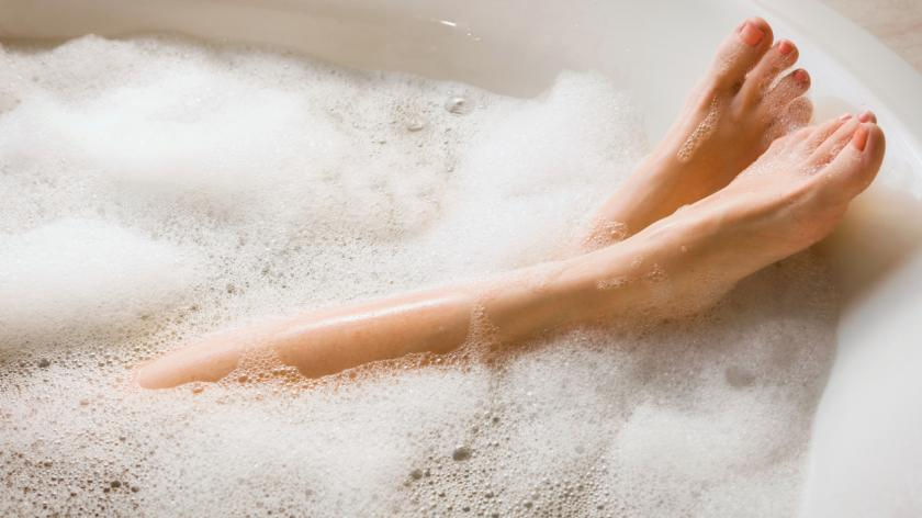 Women's legs in bubble bath